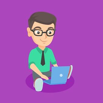 Kaukasischer kindergeschäftsmann, der an einem laptop arbeitet.