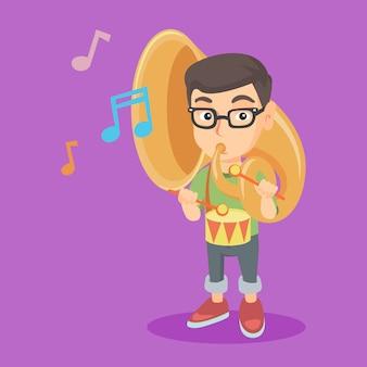 Kaukasisches kind, welches die tuba und die trommel spielt.