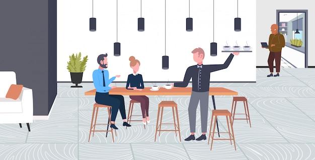 Kellner serviert getränke an geschäftsleute paar mann frau mit pause geschäftszeit kaffee punkt konzept in voller länge modernen café interieur horizontal