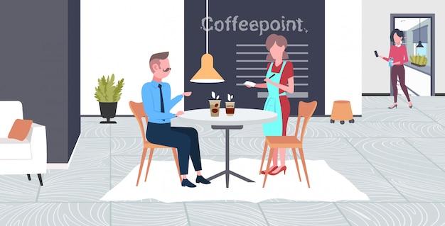 Kellnerin, die bestellung vom geschäftsmannbesucherkaffee-arbeiter in der schürze annimmt, die getränke zum mann dient, der unterbrechungsgeschäftszeitkonzept modernen kaffeepunktinnenraum in voller länge horizontal hat