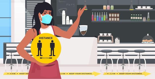 Kellnerin in der maske hält gelbes schild, das abstand hält, um horizontales porträt des coronavirus-pandemiecafés zu verhindern