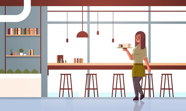 Kellnerin trägt kaffee und kuchen auf tablett