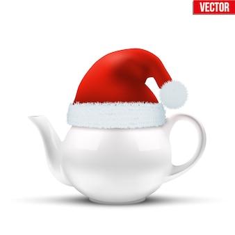 Keramische teekanne mit weihnachtsmütze des weihnachtsmannes.