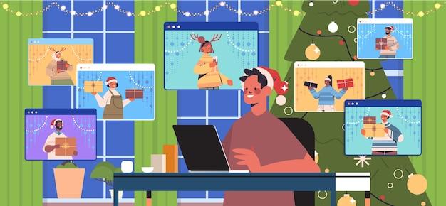 Kerl in der weihnachtsmannmütze unter verwendung des laptops, der mit mischrassenfreunden in webbrowserfenstern windows frohe weihnachten neujahrsfeiertagsfeierkonzept wohnzimmerinnenraum horizontale porträtvektorillustration diskutiert