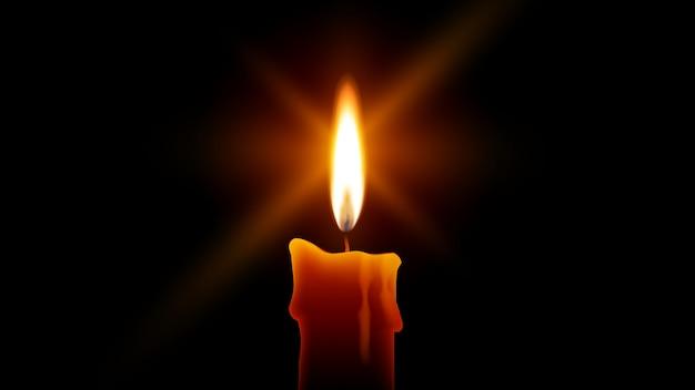 Kerzenflamme brennt im dunkeln. gelbe kerze lokalisiert auf schwarzem hintergrund. feuer mit sternen platzt linseneffekt