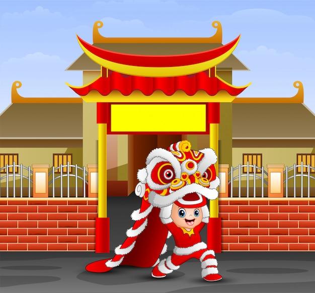 Kind, das chinesischen drachetanz vor dem tempel spielt