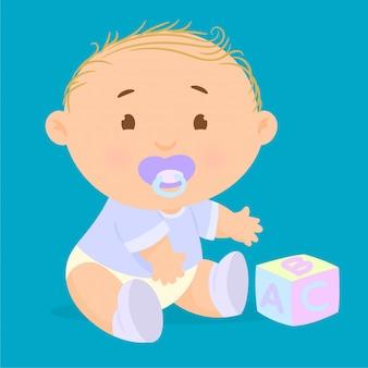 Kind mit einem schnuller im mund spielt mit block