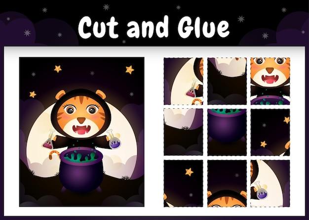Kinder-brettspiel schneiden und kleben mit einem süßen tiger mit halloween-kostüm