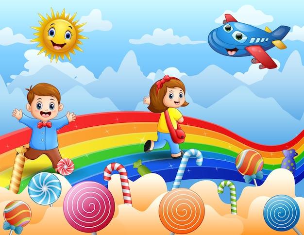 Kinder, die auf einem regenbogen- und bonbonhintergrund gehen