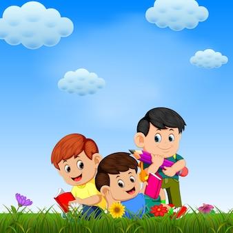 Kinder, die das buch im garten am sonnigen tag spielen und lesen