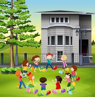 Kinder, die den ballon knallend im park spielen