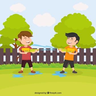 Kinder, die im garten mit plastikwassergewehren spielen