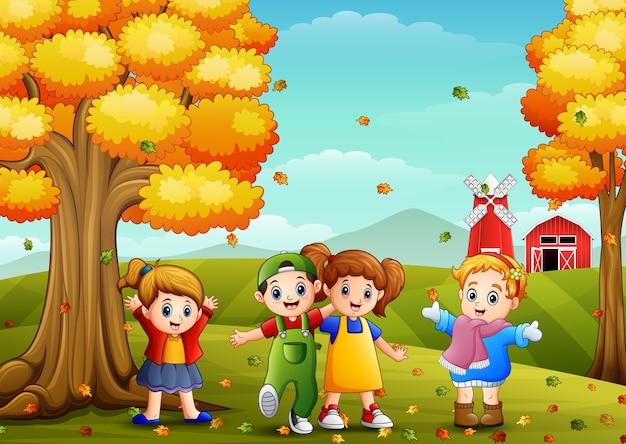 Kinder, die in der bauernhoflandschaft am herbst spielen