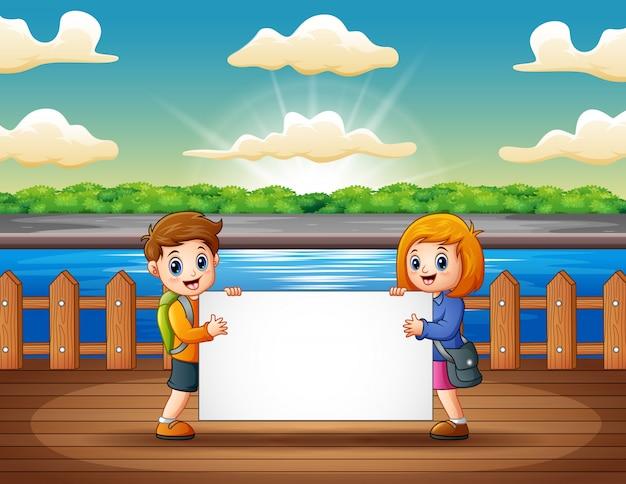 Kinder, die leeres zeichen am hölzernen pier halten