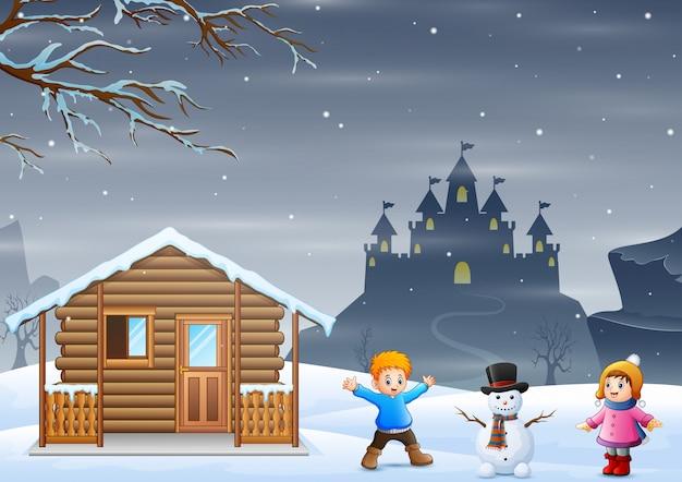 Kinder, die schneemann in der schneebedeckten landschaft machen