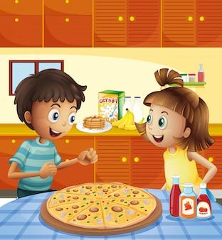Kinder in der küche mit einer ganzen pizza am tisch