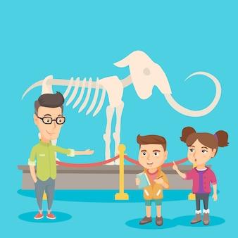 Kinder mit einem lehrer, der ein skelett im museum studiert.