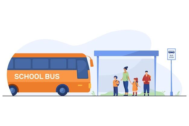 Kinder mit lehrer warten auf bus an bushaltestelle