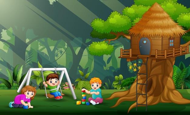 Kinder spielen im park unter dem baumhaus