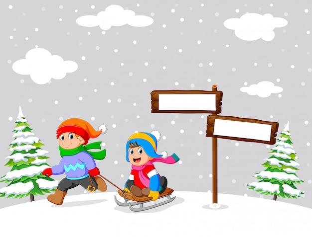 Kinder spielen im winter eine schlittenfahrt