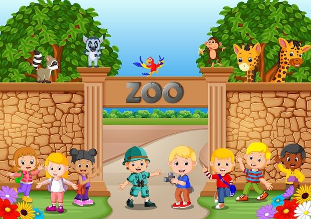 Kinder spielen im zoo mit tierpfleger und tier