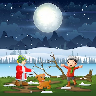 Kinder spielen in der winternachtlandschaft