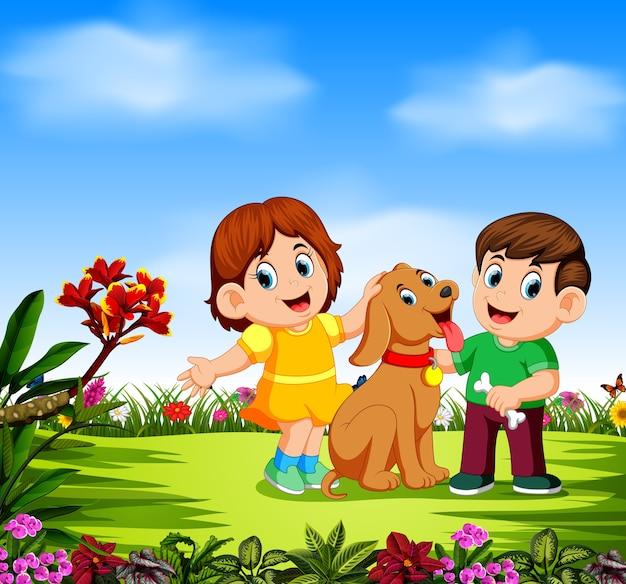 Kinder spielen mit ihrem hund um die blumen herum