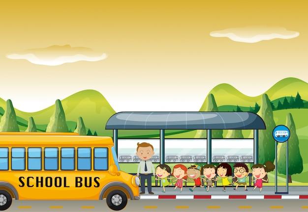 Kinder steigen an der bushaltestelle in den schulbus