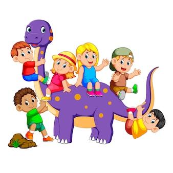 Kinder steigen in den bronosaurus ein und spielen auf seinem körper einige von denen, die seinen schwanz halten