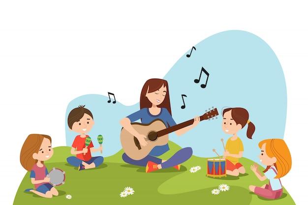 Kinder und lehrer sitzen auf gras und spielen
