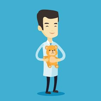 Kinderarzt arzt hält teddybär.