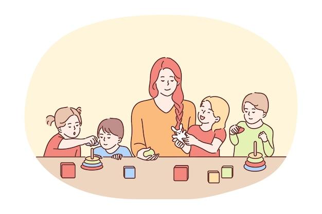 Kindermädchen im kindergarten, babysitter, babysitter-konzept. babysitter oder kindermädchen der jungen lächelnden fraukarikaturfigur, die mit der gruppe der kleinen kinder am tisch spielt. schwester, mutter, eltern