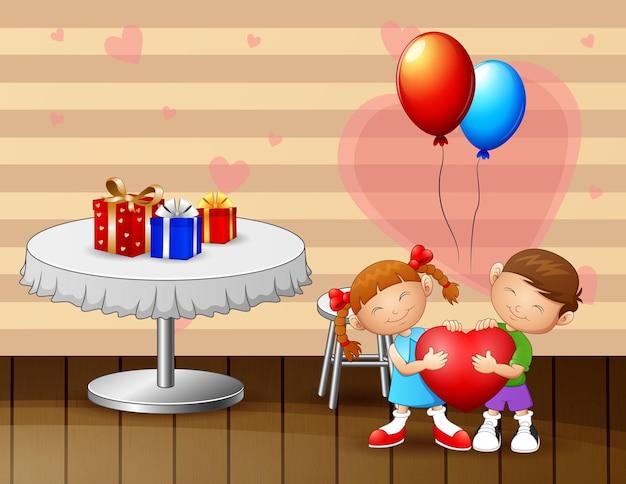 Kinderpaar jungen und mädchen, die ein rotes herz am valentinstag halten