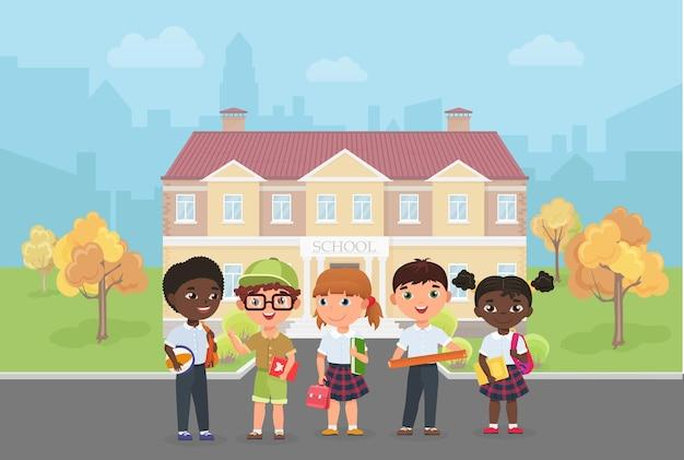 Kinderstudenten stehen vor der schule, die eine vielfältige gruppe von kindern baut, die bereit sind, zu lernen