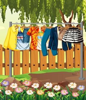 Kleidung, die an einer wäscheleine mit zaun und blume in der gartenszene hängt