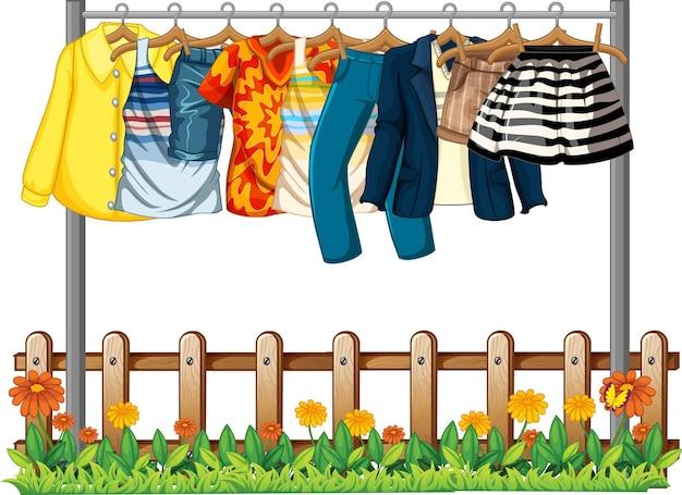 Kleidung, die an einer wäscheleine mit zaun- und blumenelementen auf weißem hintergrund hängt
