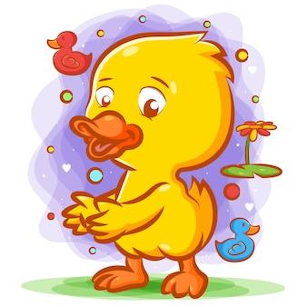 Kleine gelbe ente, die auf dem grünen gras mit dem glücklichen gesicht tanzt