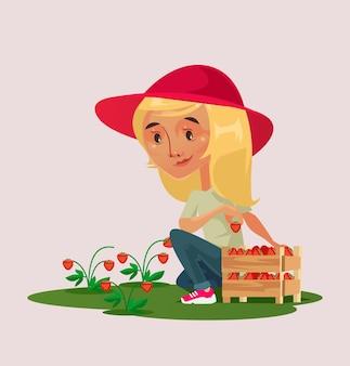 Kleine glückliche lächelnde mädchenbauerngärtnerfigur, die erdbeerbeere im korb auf grünem feld auswählt.