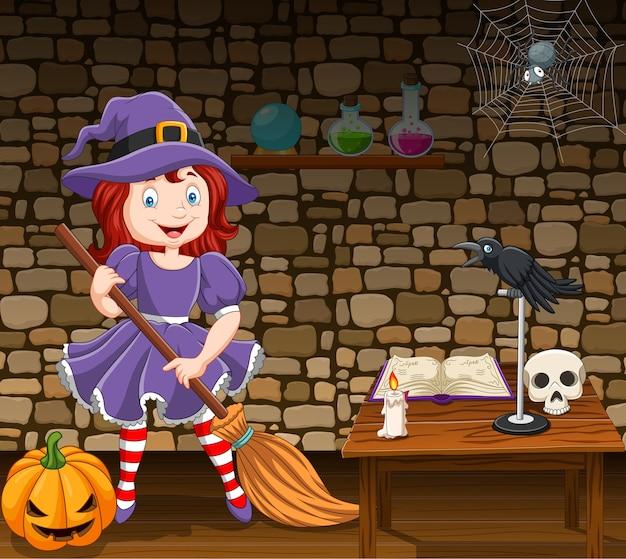 Kleine hexe der karikatur, die einen besenstiel hält