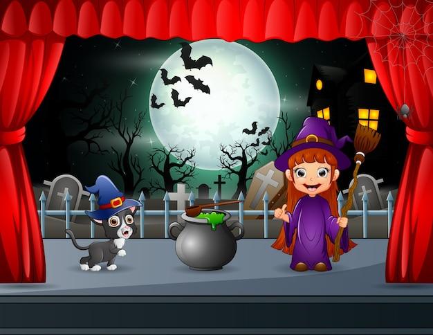 Kleine hexe und schwarze katze, die auf der bühne auftreten