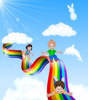 Kleine kinder der karikatur, die dia auf regenbogen spielen