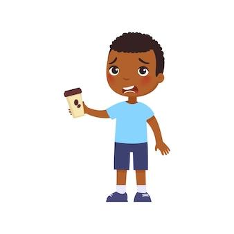 Kleiner afrikanischer junge mit kaffee unglückliches kind mit bitterem energy-drink