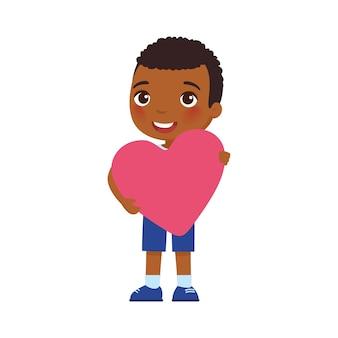 Kleiner freund, der herzförmige valentinsgrußgrußkarte hält.