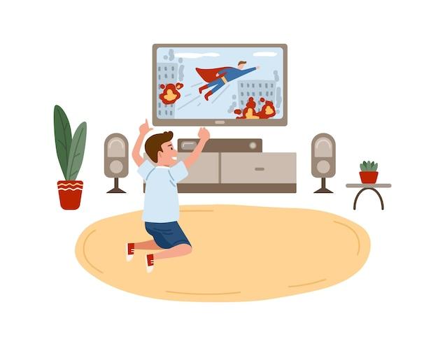 Kleiner junge, der auf boden sitzt und superheldenfilm auf fernsehgerät sieht