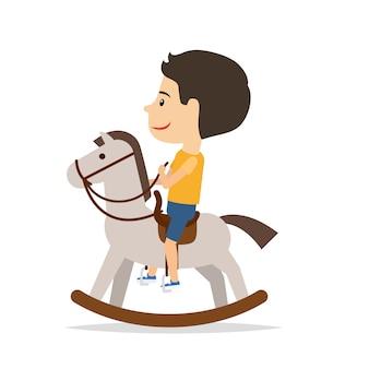 Kleiner junge, der auf pferdespielzeug sitzt