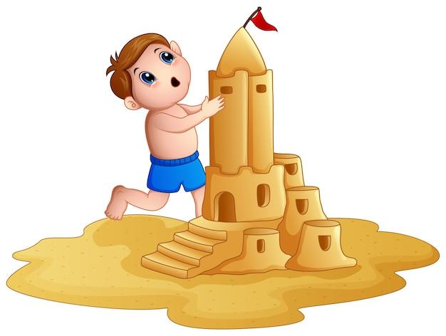 Kleiner junge, der eine große sandburg am strand macht