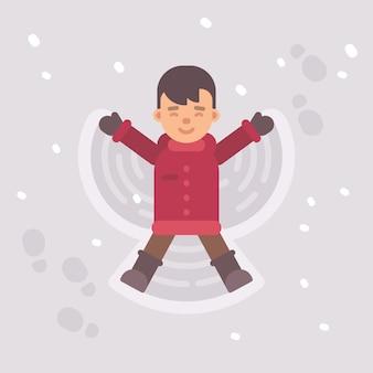 Kleiner junge, der einen schneeengel macht
