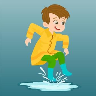 Kleiner junge, der gelben regenmantel trägt