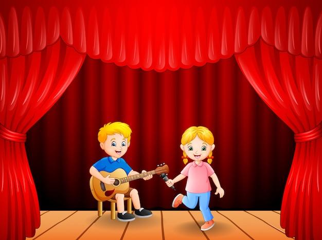 Kleiner junge, der gitarre spielt und mädchentanzen singt