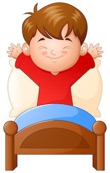 Kleiner junge, der in einem bett auf weißem hintergrund aufwacht